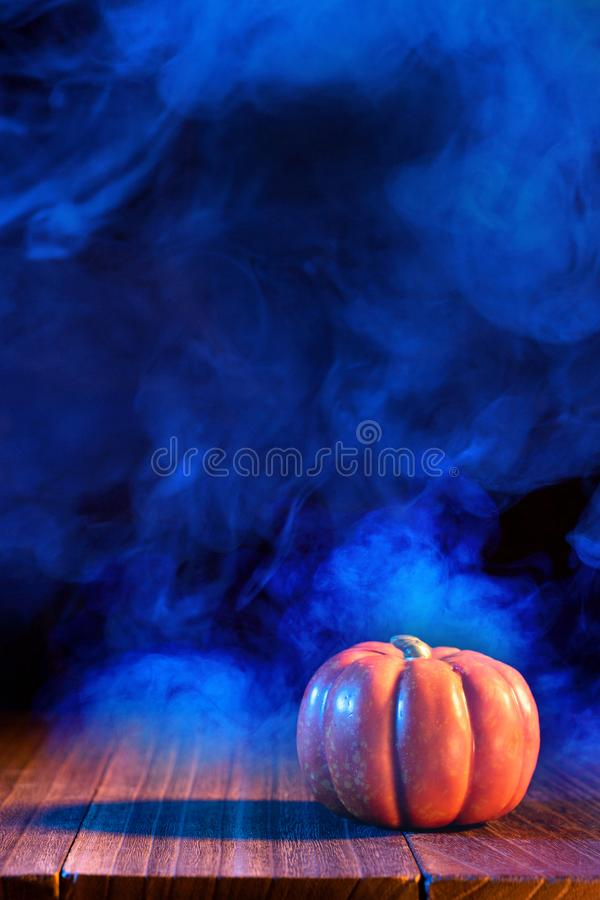 Halloween concept - Orange pumpkin lantern on a dark wooden table with double colored smoke around the background, trick or treat. Close up royalty free stock image