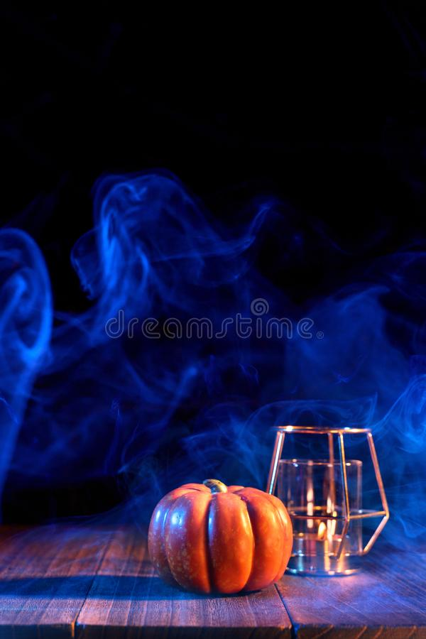 Halloween concept - Orange pumpkin lantern on a dark wooden table with double colored smoke around the background, trick or treat. Close up stock photos