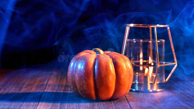Halloween concept - Orange pumpkin lantern on a dark wooden table with double colored smoke around the background, trick or treat. Close up stock photo