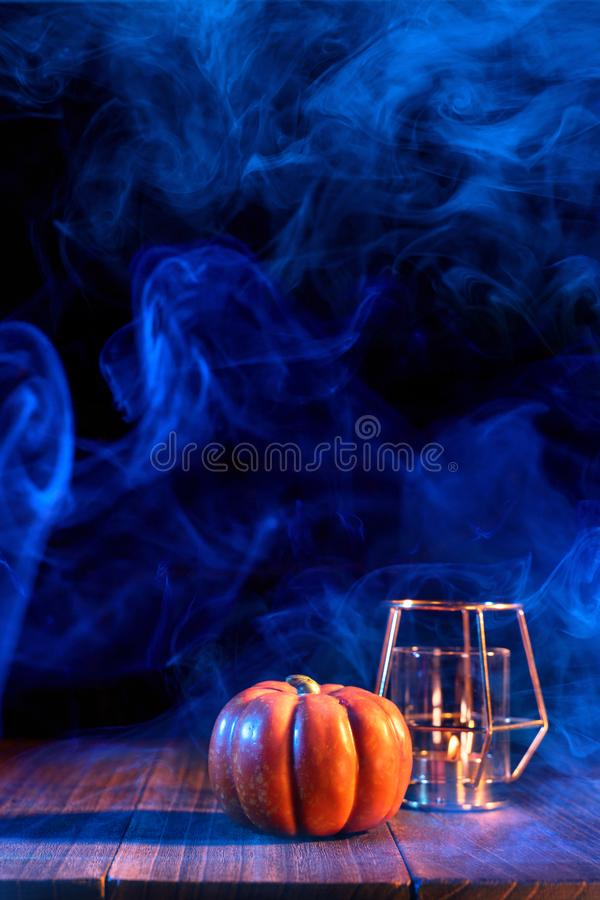 Halloween concept - Orange pumpkin lantern on a dark wooden table with double colored smoke around the background, trick or treat. Close up royalty free stock photos