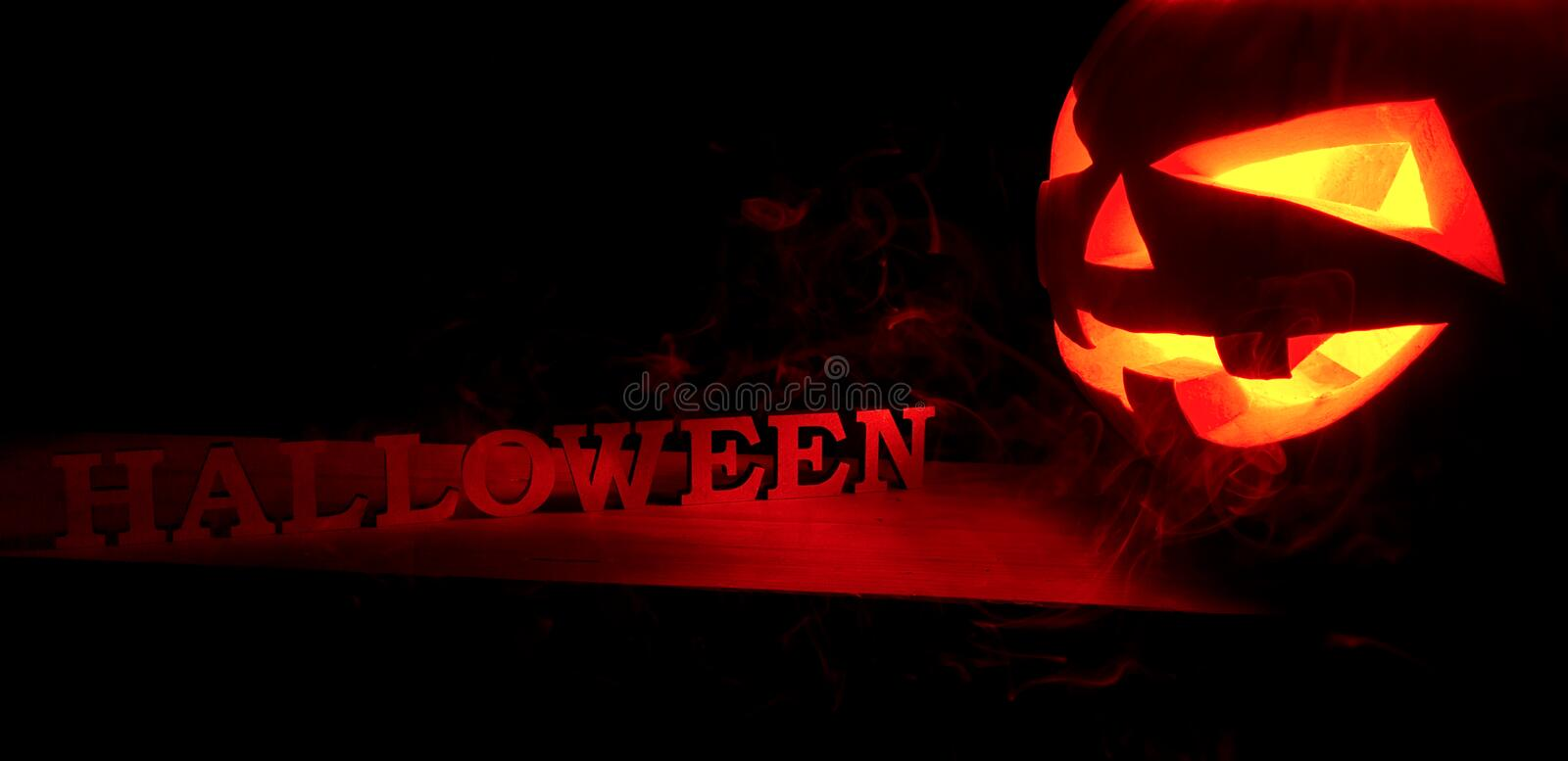 Halloween concept. Scary spooky pumpkin with Halloween inscription, with a hot fire glow and smoke, a poster for a party stock photos