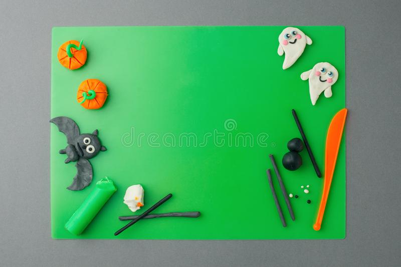 Halloween concept. symbols and decorations made of polymer clay on green table flat lay top view, copy space, creative seasonal stock image