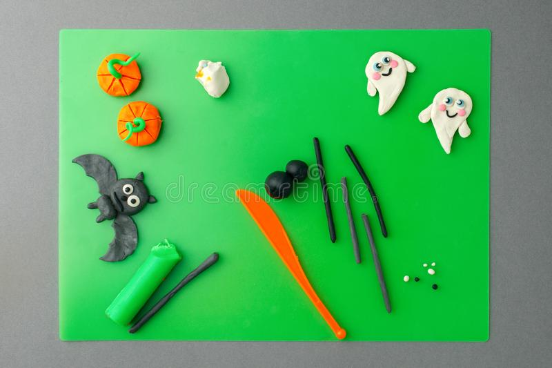 Halloween concept. symbols and decorations made of polymer clay on green table flat lay top view, copy space, creative seasonal. Holiday DIY idea for kids royalty free stock photography