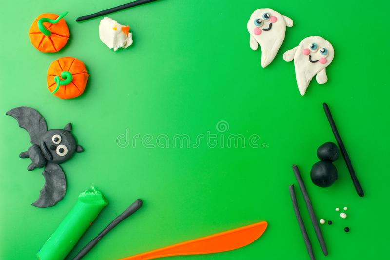 Halloween concept. symbols and decorations made of polymer clay on green table flat lay top view, copy space, creative seasonal. Holiday DIY idea for kids stock photos