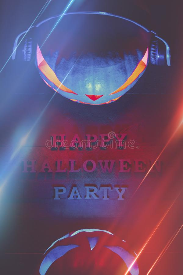 Halloween concept. Two pumpkins in headphones, with a warm and cold glow, a poster for a party with an inscription. Halloween concept. Two pumpkins in headphones royalty free stock image