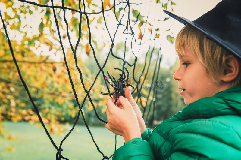Halloween-concept weinig jongen met spin en Webspel bij daling stock afbeelding