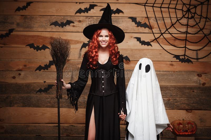 Halloween Concept - Witch mother and little white ghost doing trick or treat celebrating Halloween posing with curved pumpkins ove stock photos