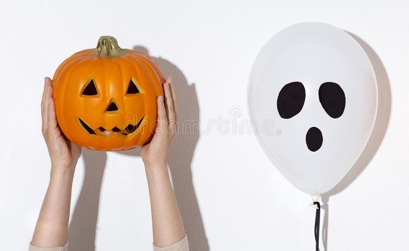 Ghost Balloon and pumpkin in woman hands on white stock image