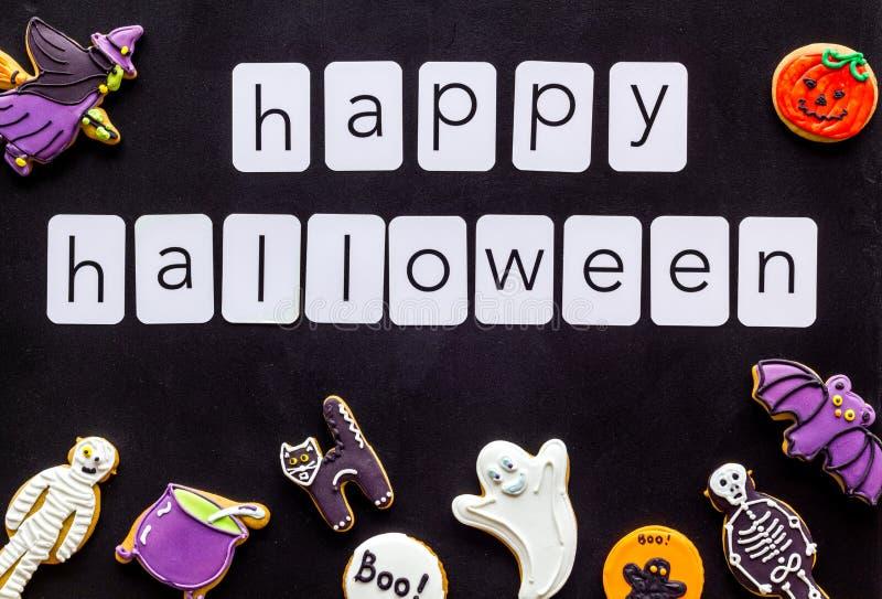 Halloween cookies frame in shape of spooky figures with happy halloween copy on black background top view. Halloween cookies frame in shape of spooky mystic stock image