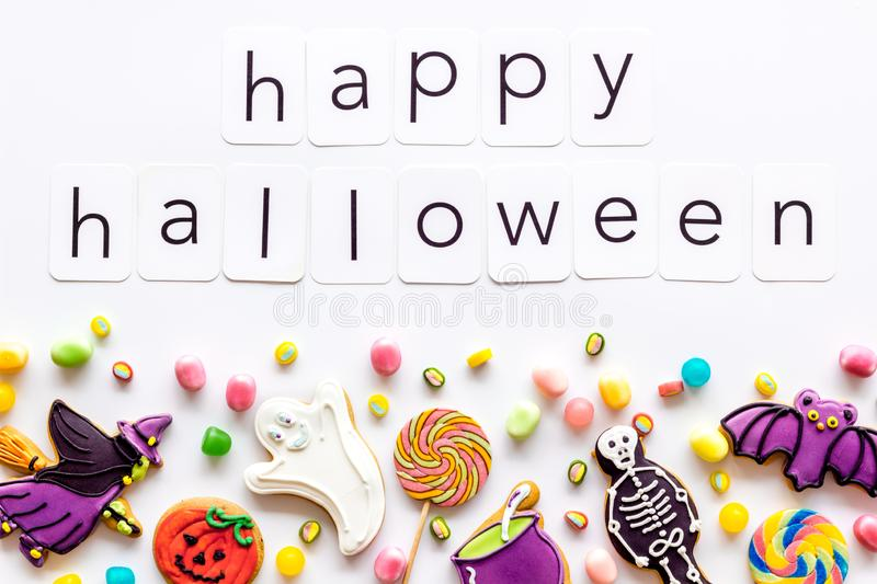 Halloween cookies frame in shape of spooky figures with happy halloween copy on white background top view. Halloween cookies frame in shape of spooky mystic royalty free stock images