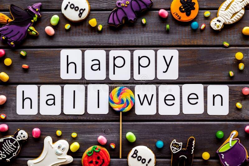 Halloween cookies frame in shape of spooky figures with happy halloween copy on wooden background top view. Halloween cookies frame in shape of spooky mystic stock photo