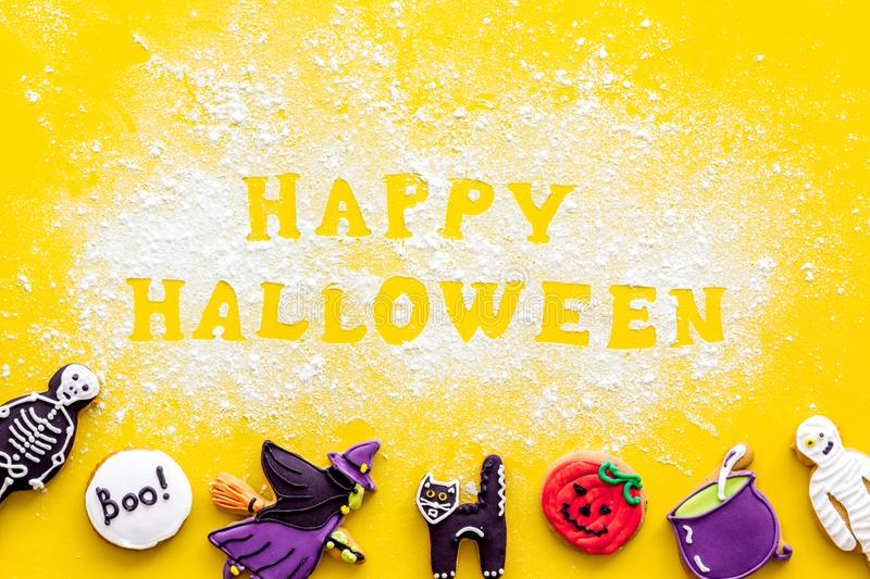 Halloween cookies frame in shape of spooky figures with happy halloween copy on yellow background top view. Halloween cookies frame in shape of spooky mystic royalty free stock photo