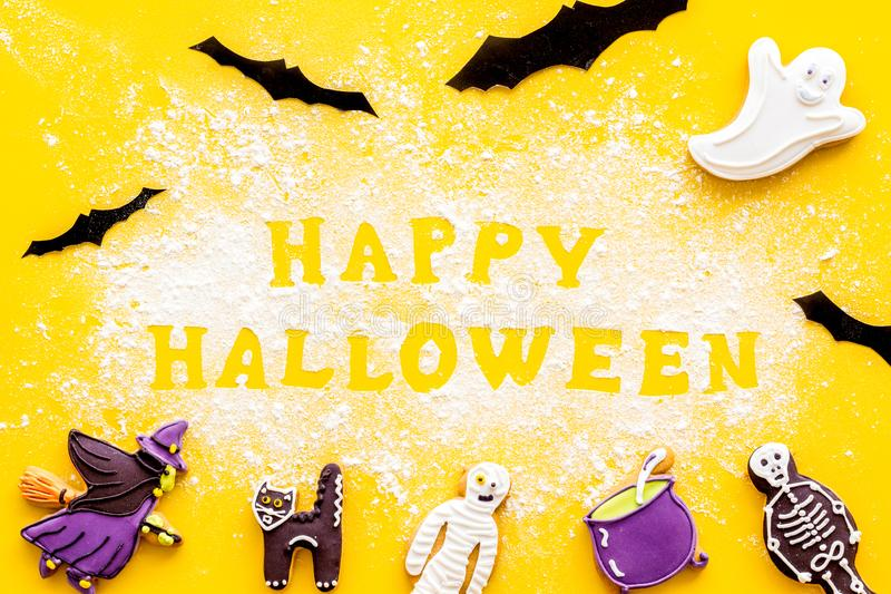 Halloween cookies frame in shape of spooky figures with happy halloween copy on yellow background top view. Halloween cookies frame in shape of spooky mystic royalty free stock image