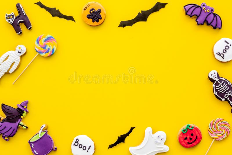 Halloween cookies in shape of spooky figures frame on yellow background top view mock up. Halloween cookies in shape of spooky mystic figures and characters royalty free stock images