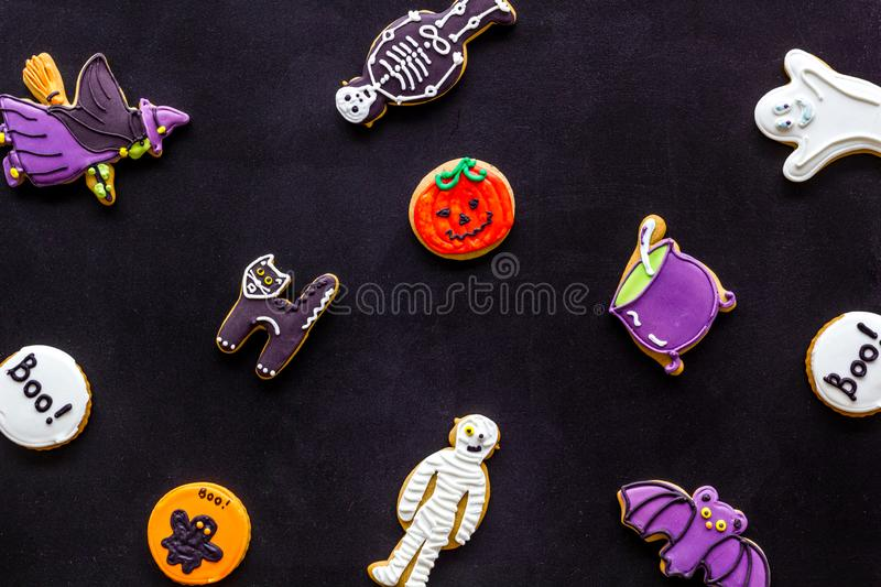 Halloween cookies in shape of spooky figures pattern on black background top view. Halloween cookies in shape of spooky mystic figures and characters pattern on royalty free stock image