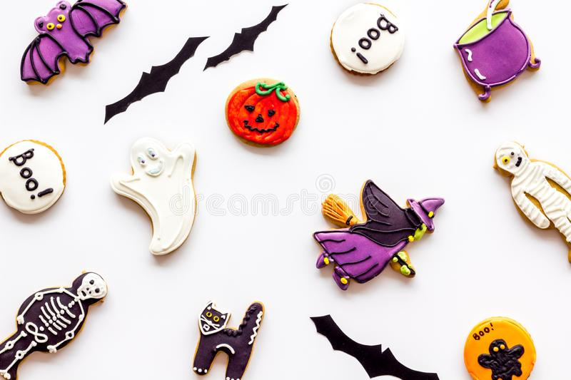 Halloween cookies in shape of spooky figures pattern on white background top view. Halloween cookies in shape of spooky mystic figures and characters pattern on royalty free stock images