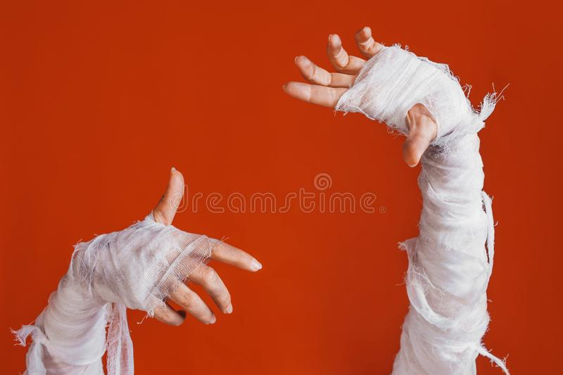 Halloween, costume image. The mummy`s hand in bandages making gestures. Mummy makes a frame for your label, copy space royalty free stock photos