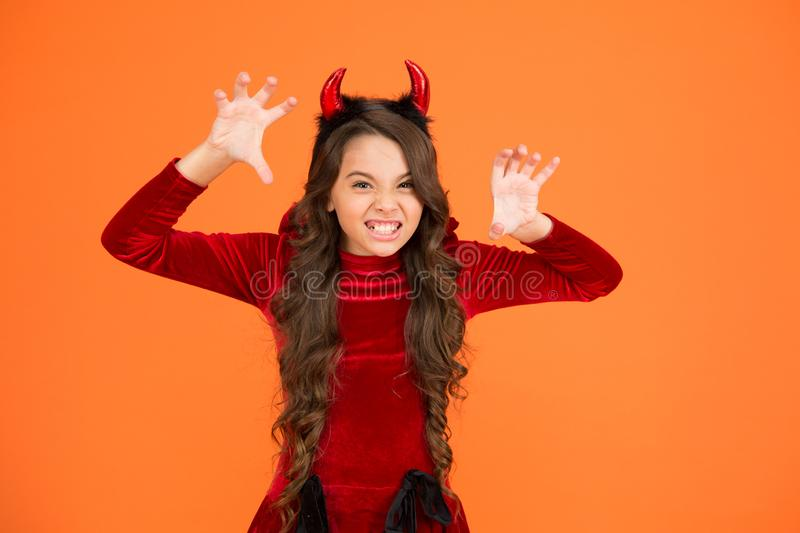 Halloween costumes designed after supernatural figures. Little devil. Little girl red horns celebrate Halloween. Carnival concept. Small child with imp style stock photo