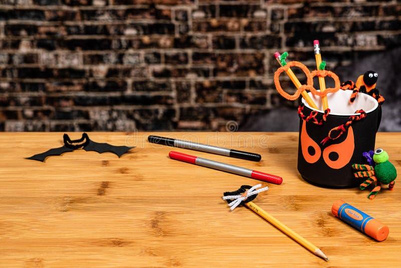 Halloween Crafting met een spooky potlood beker en een paar pijpreinigende wezens. Negatieve ruimte voor copywriting stock foto's