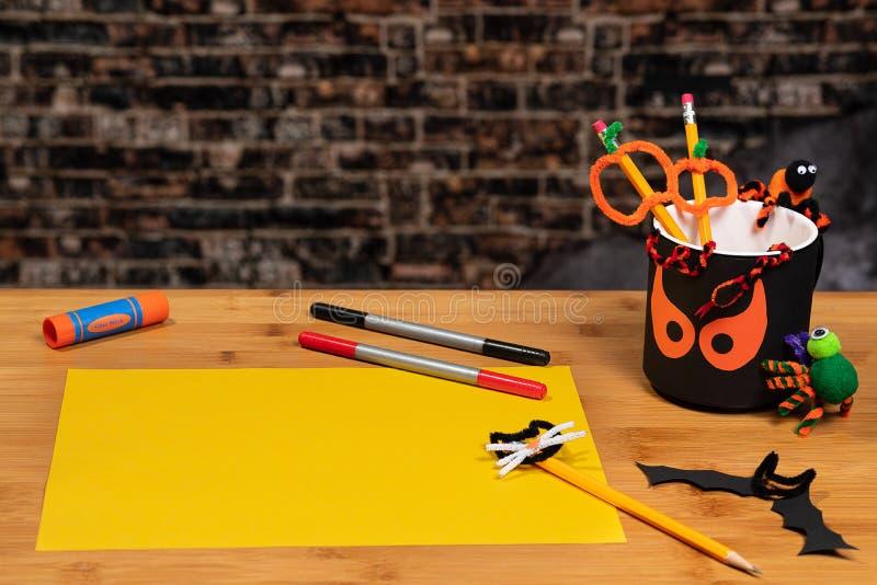 Halloween Crafting mit einem sprichwörtlichen Bleistiftbecher und einem leeren Blatt gelben Baupapiers, fertig. Es gibt reichlich stockfotos