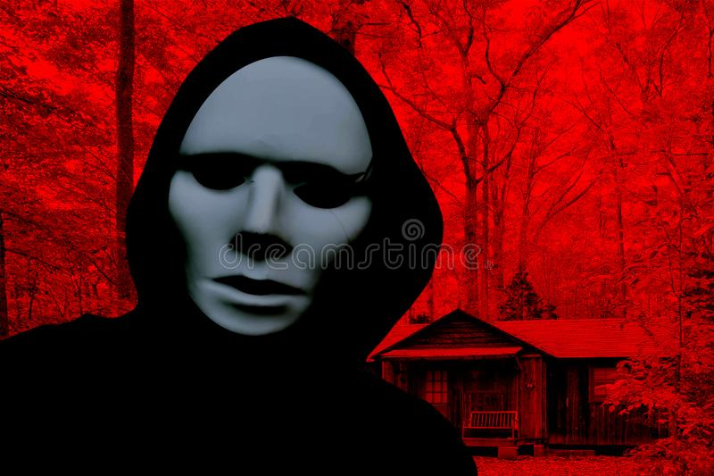Halloween creepy masked person wearing a hood and standing in front of a cabin in a horror forest stock image