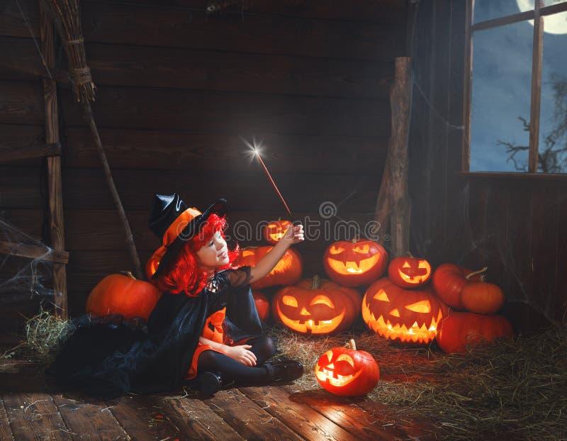 Halloween criança da bruxa com varinha e as abóboras mágicas fotografia de stock
