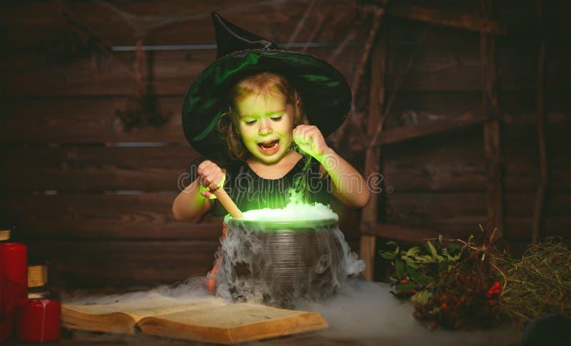 Halloween criança pequena da bruxa que cozinha a poção no caldeirão com imagens de stock