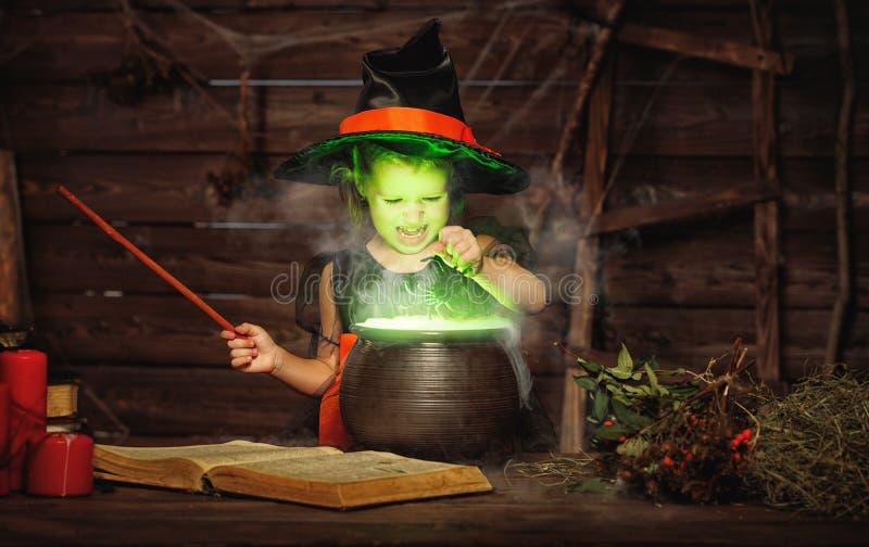 Halloween criança pequena da bruxa que cozinha a poção no caldeirão com fotografia de stock royalty free