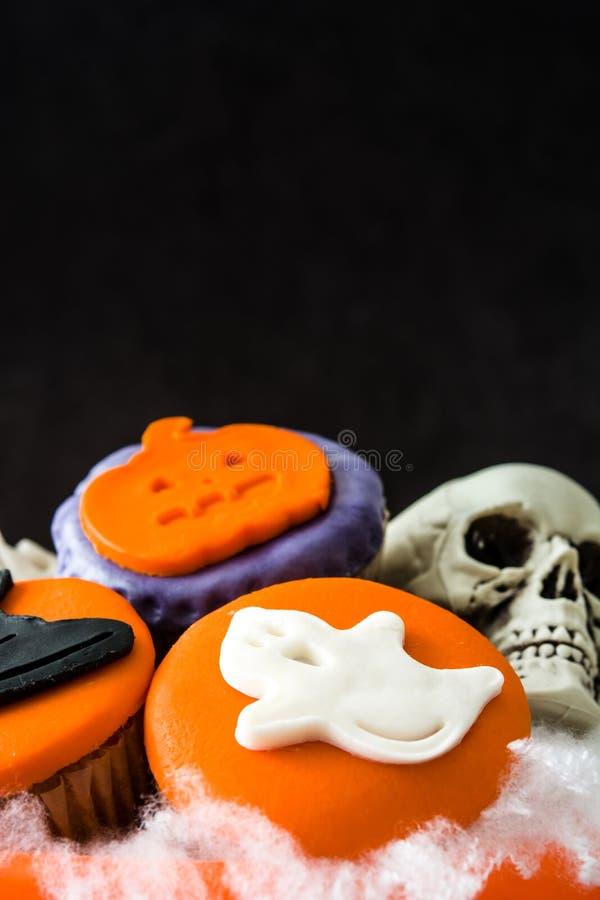 Halloween cupcakes in een mand met pompoenvorm stock foto's