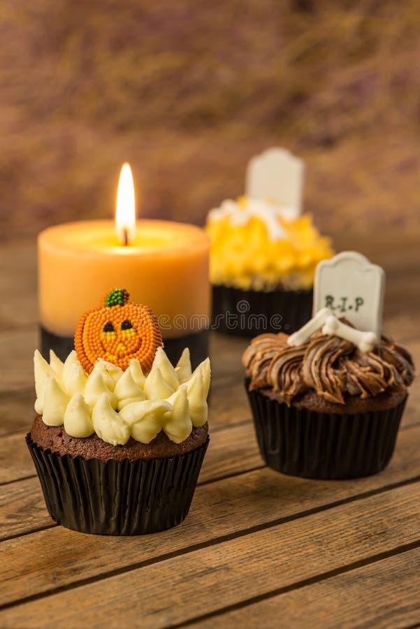 Halloween cupcakes en een brandende kaars op een oude rustieke houten lijst royalty-vrije stock fotografie