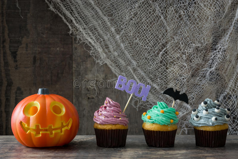 Halloween cupcakes en pompoen op rustieke houten achtergrond stock afbeeldingen