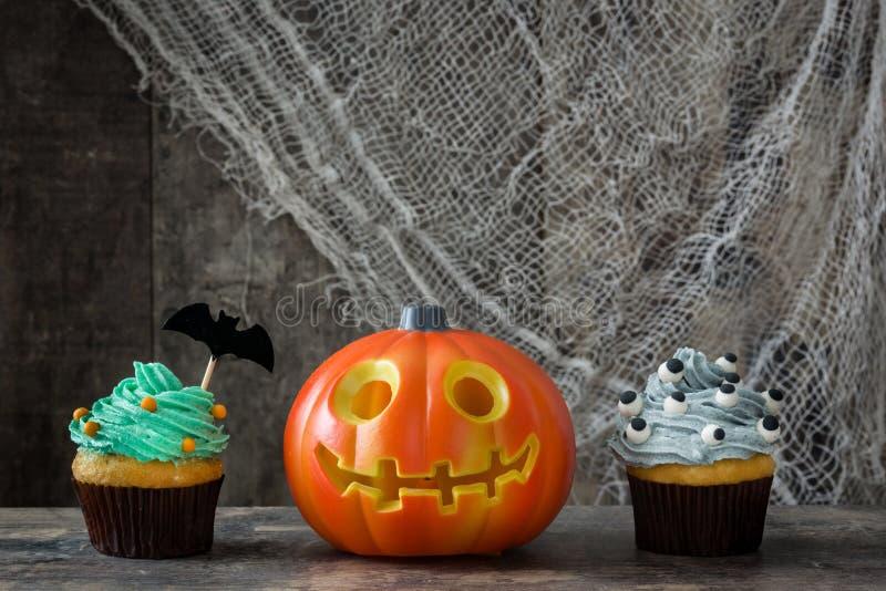 Halloween cupcakes en pompoen op rustieke houten achtergrond royalty-vrije stock afbeelding