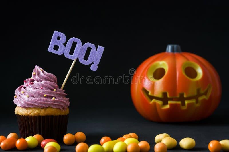 Halloween cupcakes en pompoen op zwarte achtergrond royalty-vrije stock afbeeldingen