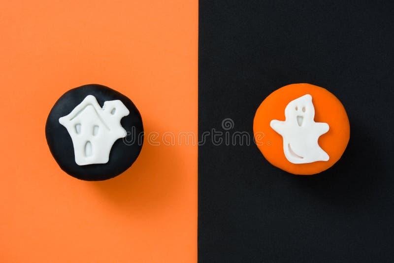 Halloween cupcakes op oranje en zwarte achtergrond stock foto's
