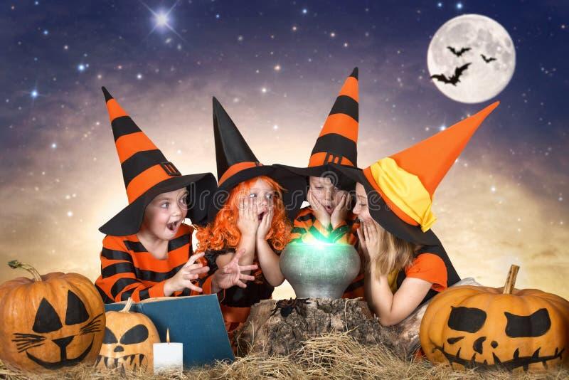 Halloween De kinderen van heksen en tovenaars die drankje in de ketel met pompoen en werktijdboek koken stock afbeeldingen