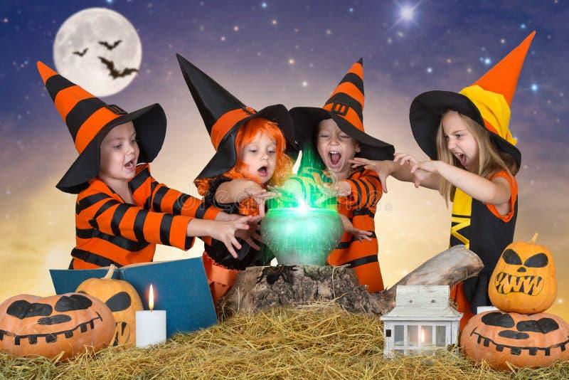 Halloween De kinderen van heksen en tovenaars die drankje in de ketel met pompoen en werktijdboek koken stock foto's