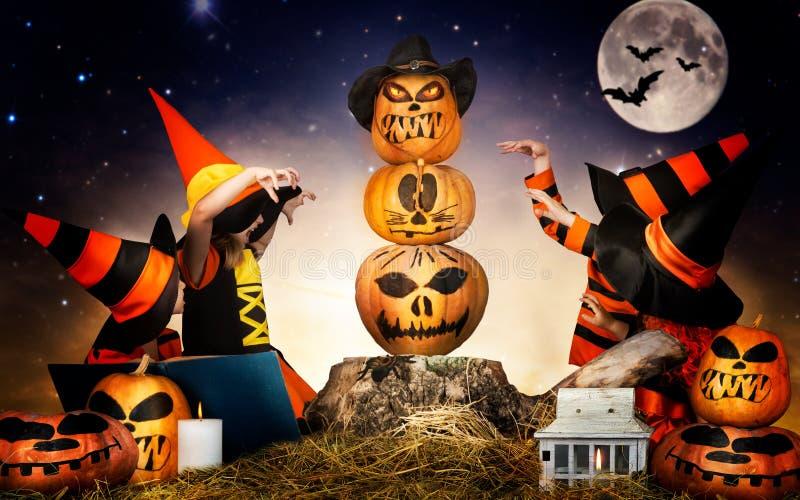 Halloween De kinderen van heksen en tovenaars toveren over de pompoen stock afbeeldingen
