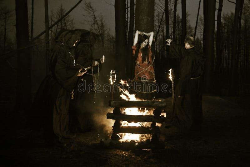Halloween De mensen in zwarte kleren, branden de heks bij de staak bij stock fotografie
