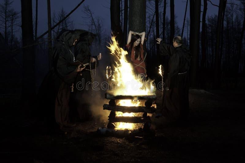 Halloween De mensen in zwarte kleren, branden de heks bij de staak bij stock afbeeldingen