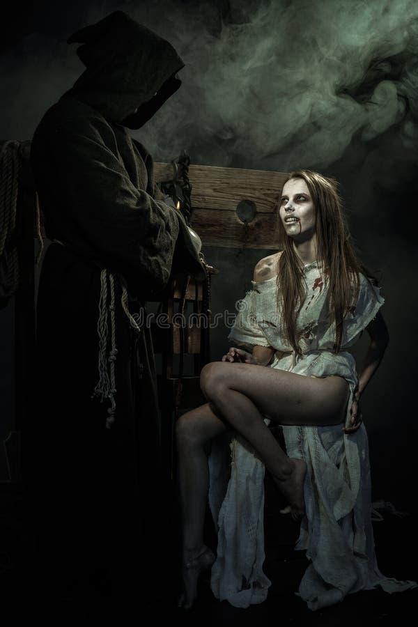 Halloween De middeleeuwen De heks verleidt een monnik stock foto's