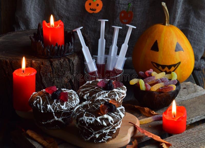 Halloween-de truc of behandelt partij Grappige heerlijke snoepjes en pompoen op houten achtergrond - muffins, cupcakes, sap, gele royalty-vrije stock foto