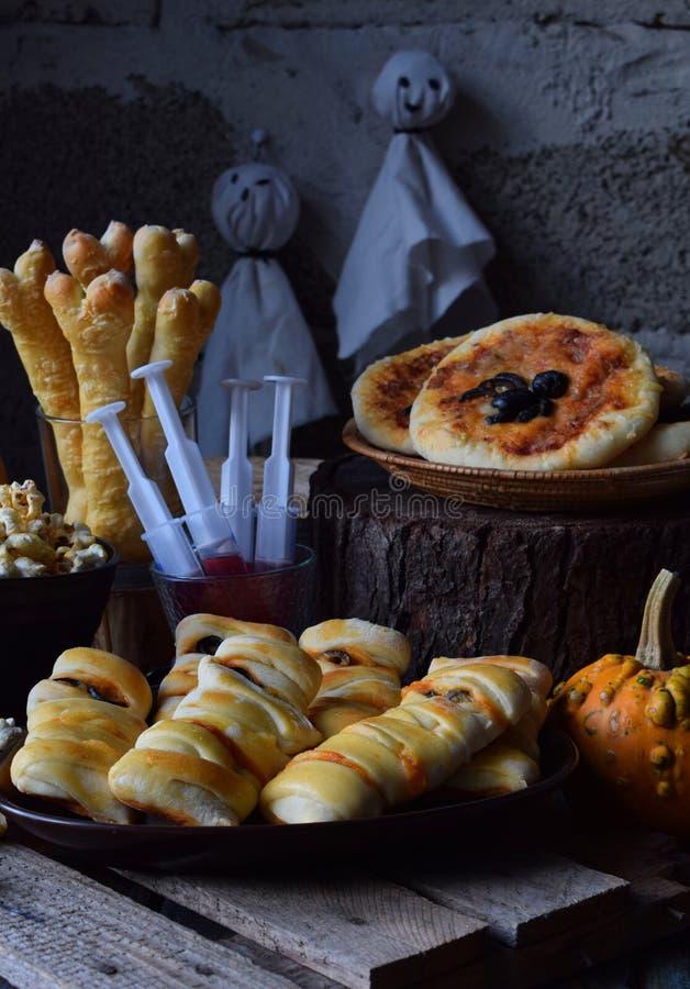 Halloween-de truc of behandelt partij Grappige heerlijke voedsel en pompoen op houten achtergrond - minipizza, broodstokken, kaas royalty-vrije stock foto's