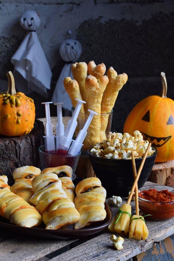 Halloween-de truc of behandelt partij Grappige heerlijke voedsel en pompoen op houten achtergrond - minipizza, broodstokken, kaas stock fotografie