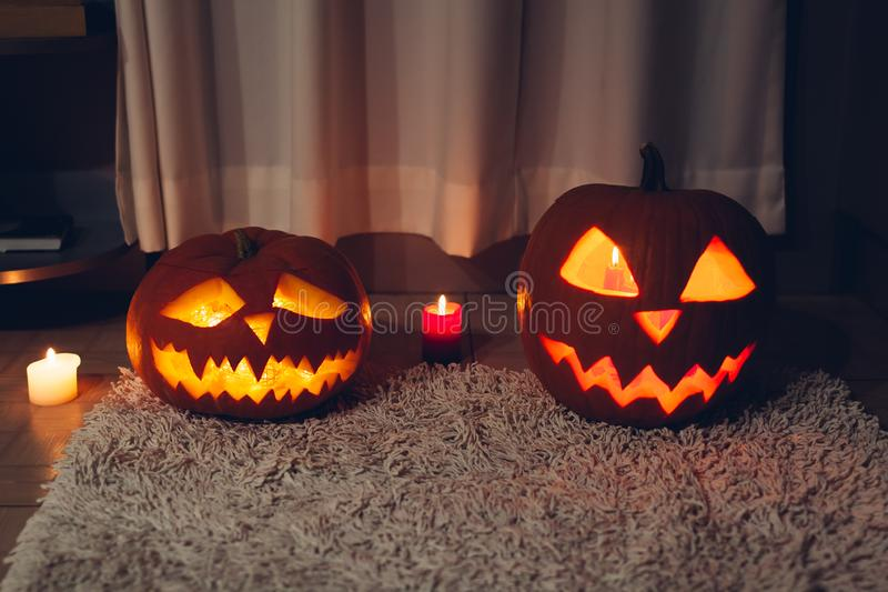 Halloween decoration. Carved pumpkins with candles on kitchen. Jack-o-lantern. royalty free stock images