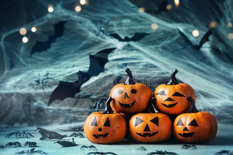 Halloween decoration with funny pumpkin heads, spider, web and flying bat on mystical bokeh background. Halloween decoration with funny pumpkin heads, spider royalty free stock image