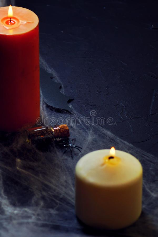 Halloween decoration with spider on web, and candles on black background. vertical royalty free stock photography