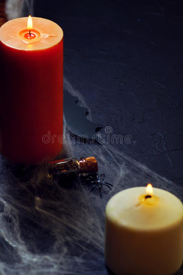 Halloween decoration with spider on web, and candles on black background. vertical stock image