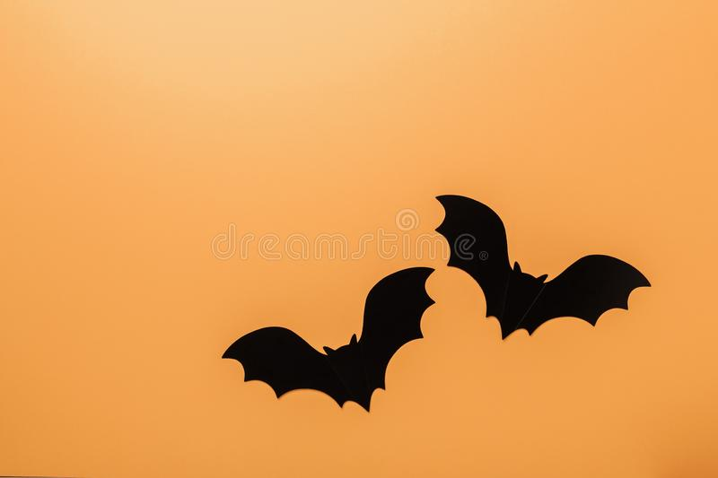 Halloween decorations concept. Black paper bats on orange background. Top view Copy space royalty free stock photo