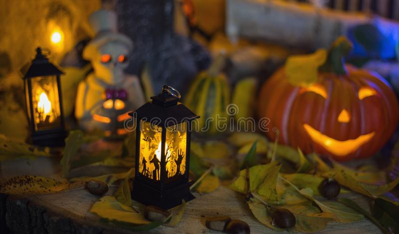 Halloween decorations concept at night. Close up of jack o`lantern, vintage lanterns, pumpkins, skull, autumn leaves royalty free stock photos