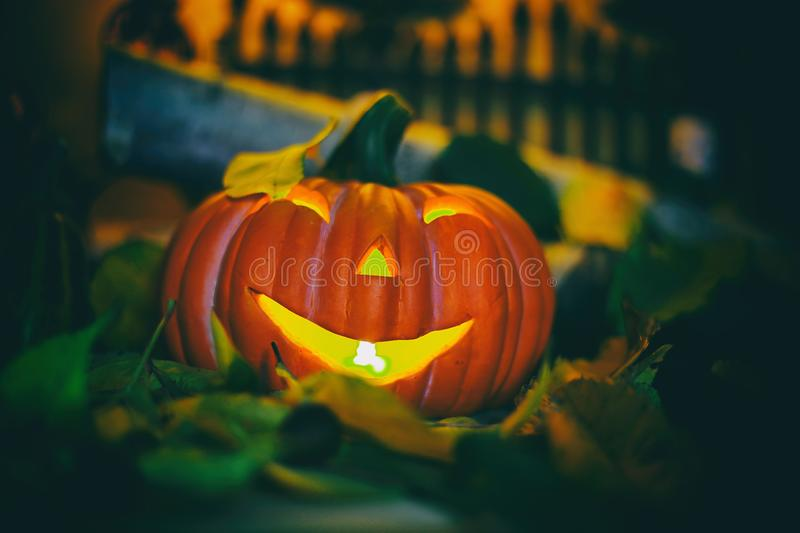 Halloween decorations concept at night. Close up of jack o`lantern, vintage lanterns, pumpkins, skull, autumn leaves stock photo